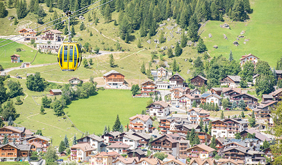 A cabin of the Boè cable car passes over the village of Corvara