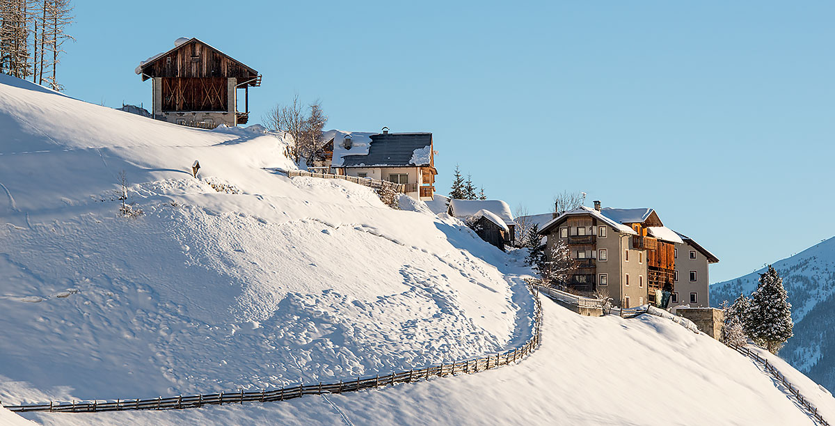 Several homes on the snowy slope of the village of Antermoia