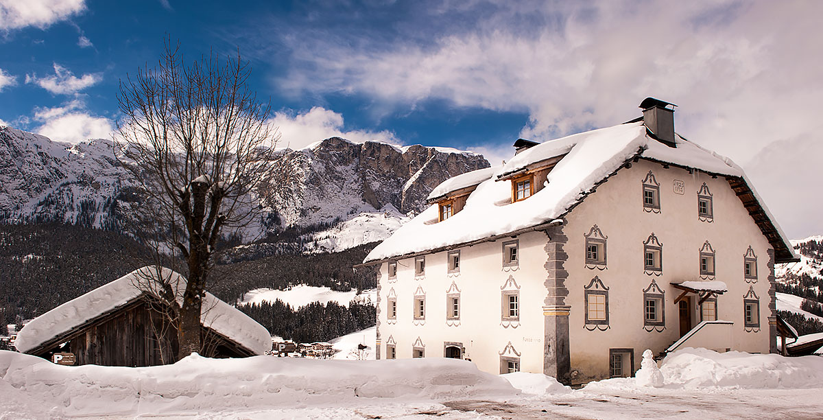 House with decorated windows and snow on the roof in the village of Badia - Pedraces