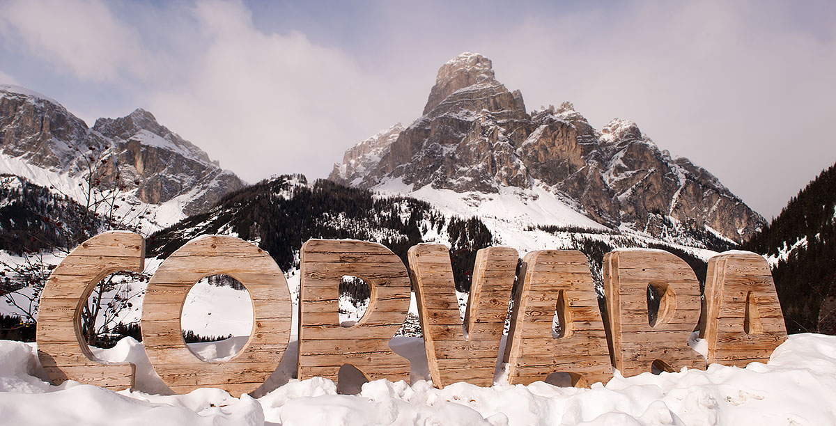 The writing Corvara made of wood surrounded by the snow