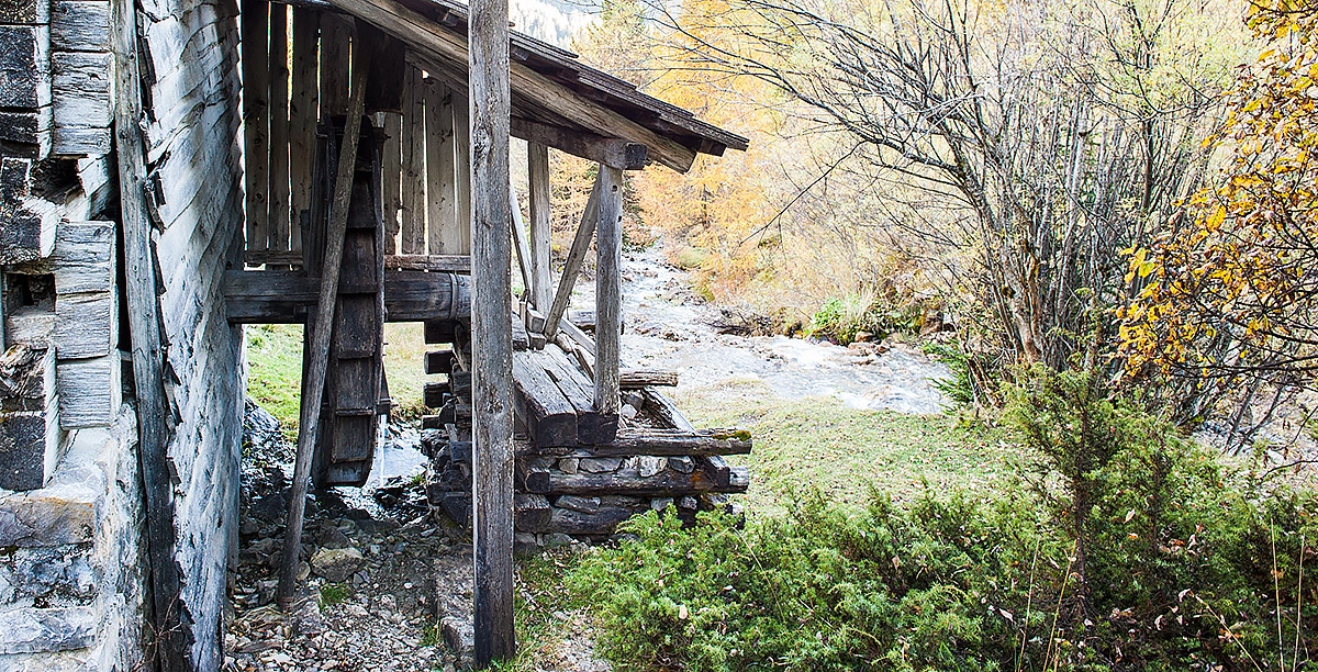 A wheel of a wooden mill beside a stream in Alta Badia