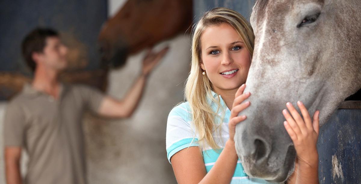 Blonde woman caresses the muzzle of a horse