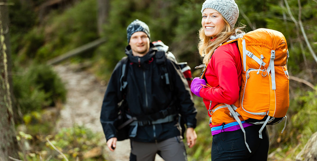 Man and woman with mountain clothing run through a path