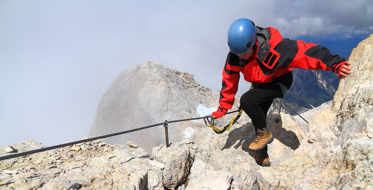 Woman on a via ferrata in the high mountains in Alta Badia