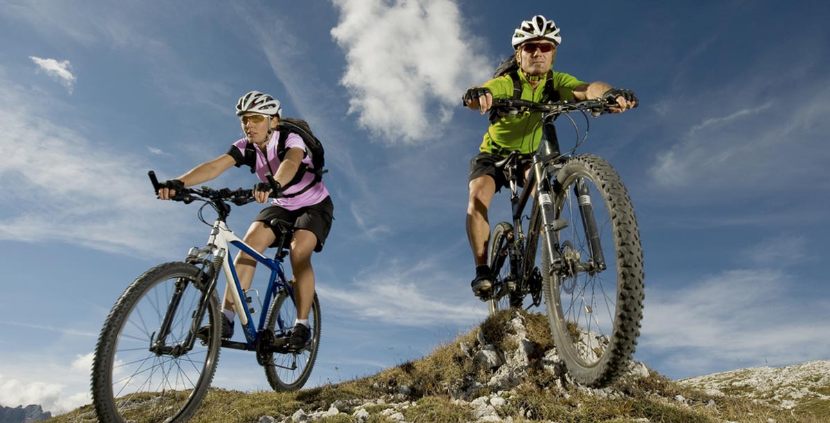 Two expert mountain bikers riding on a mountain path