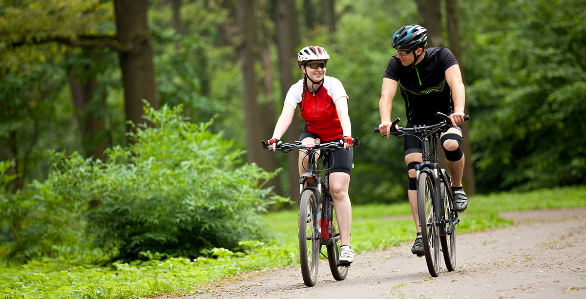 Man and woman cycling on a dirt road in the middle of the woods