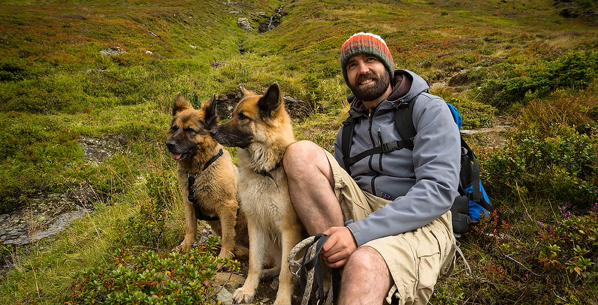Man with backpack is having a break by sitting on a green mountain meadow with his two dogs.