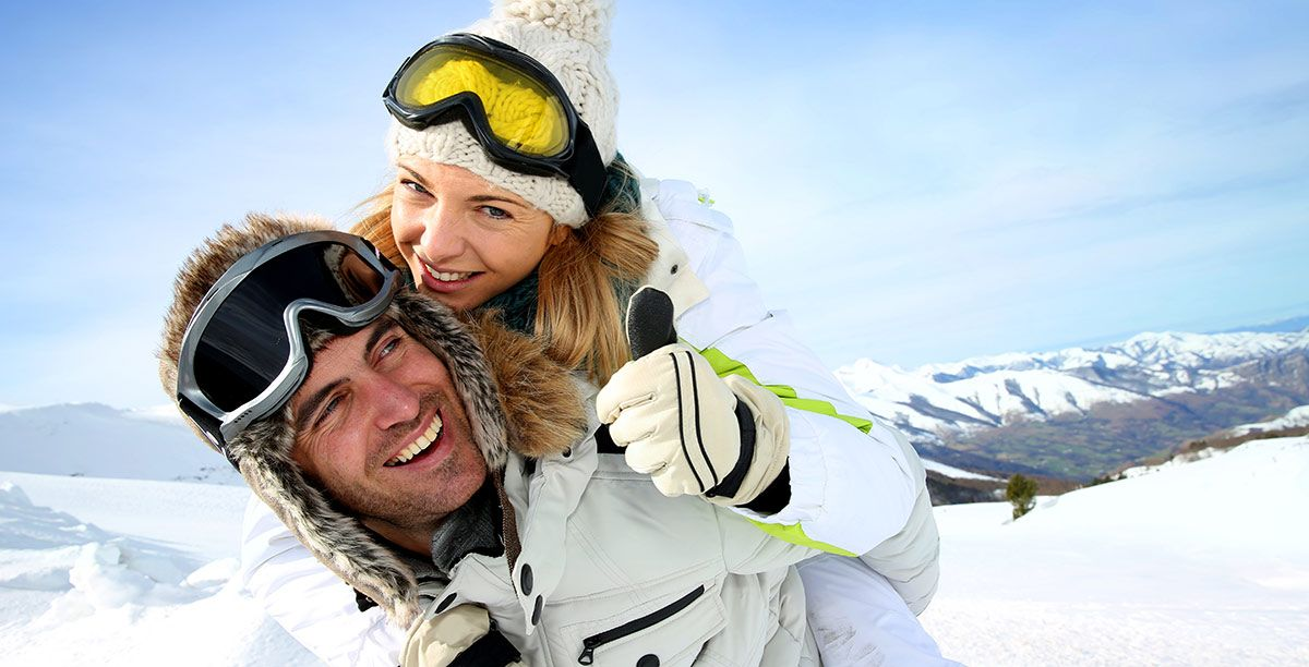 Man and woman are having fun in the snow dressed in ski clothes