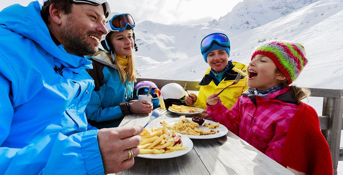 Mom, dad and two daughters eat something after skiing on the snow