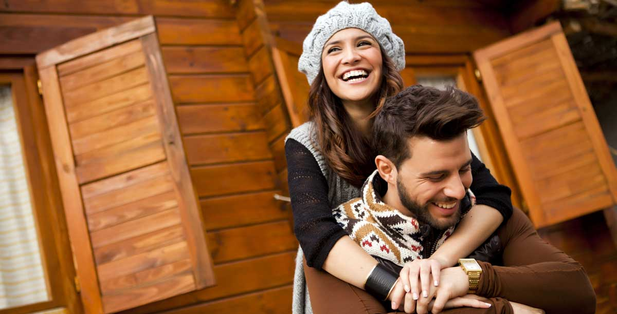 A couple smiling in front of a wooden mountain hut