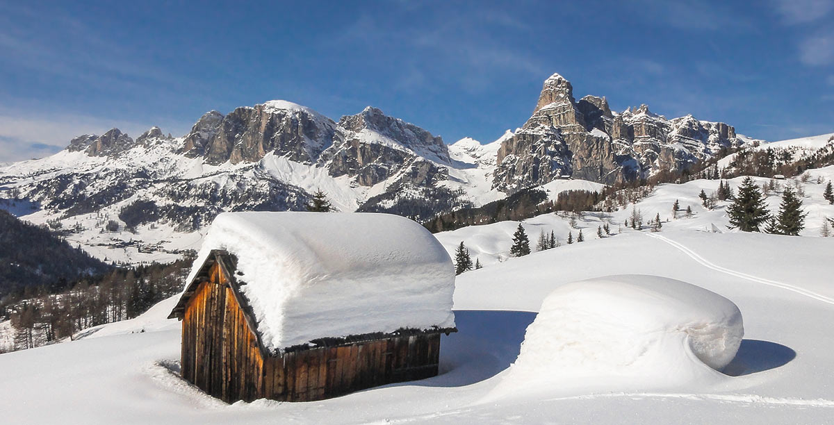 Wooden hut with a meter of snow on the roof and mountains in the background