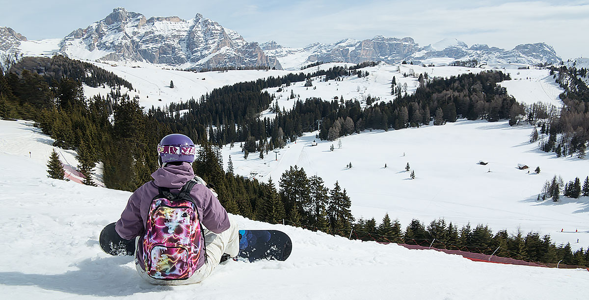 Girl with backpack, helmet and snowboard foot sitting watching the snowy mountains