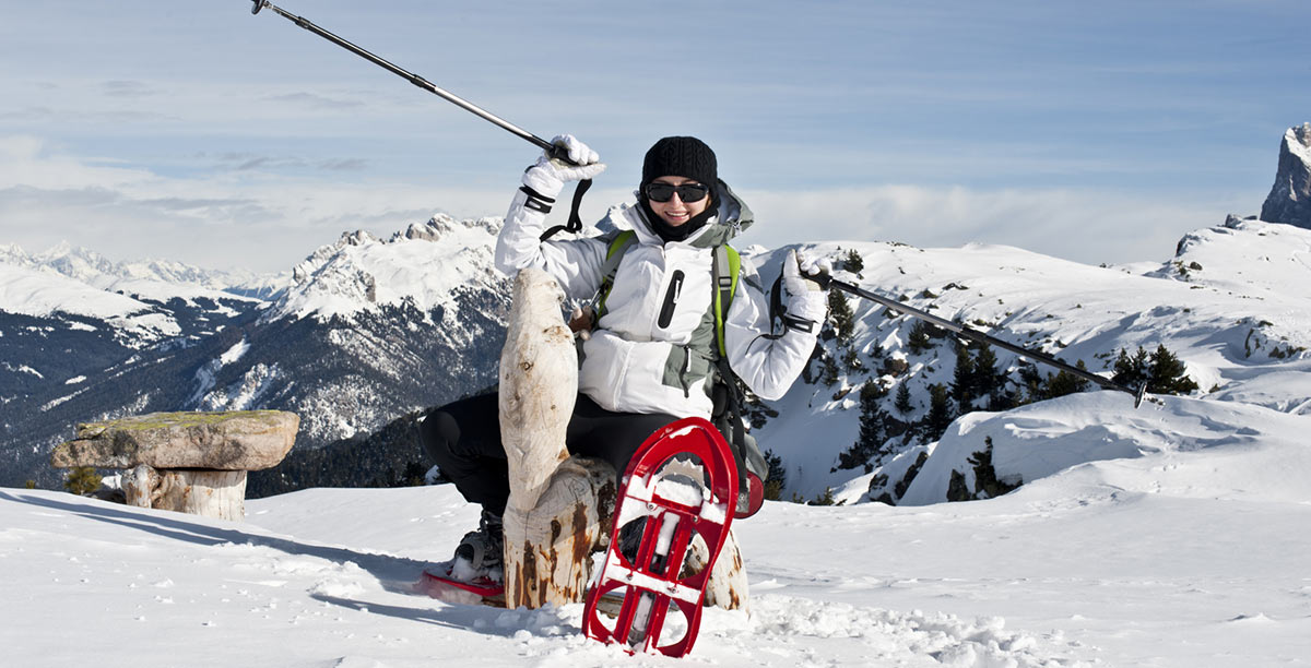 Woman with white jacket and black hat shows red snowshoes