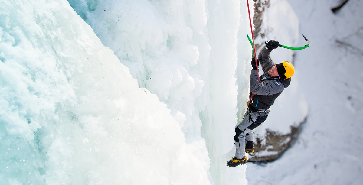 A man with a rope hanging on a wall of ice climbing