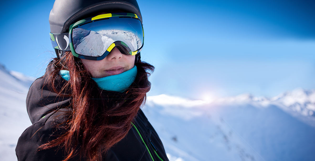 Close up of a woman with red hair, helmet and goggles ski