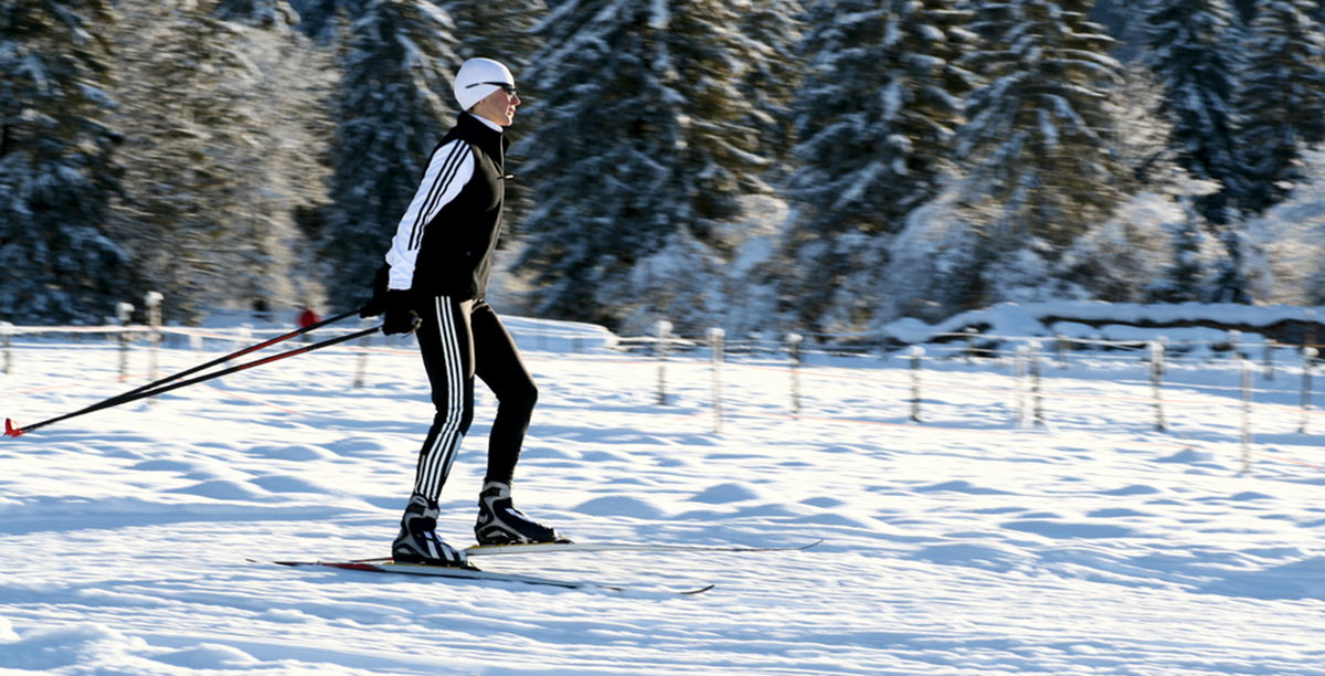 A person dressed in black and white heels with cross-country skis