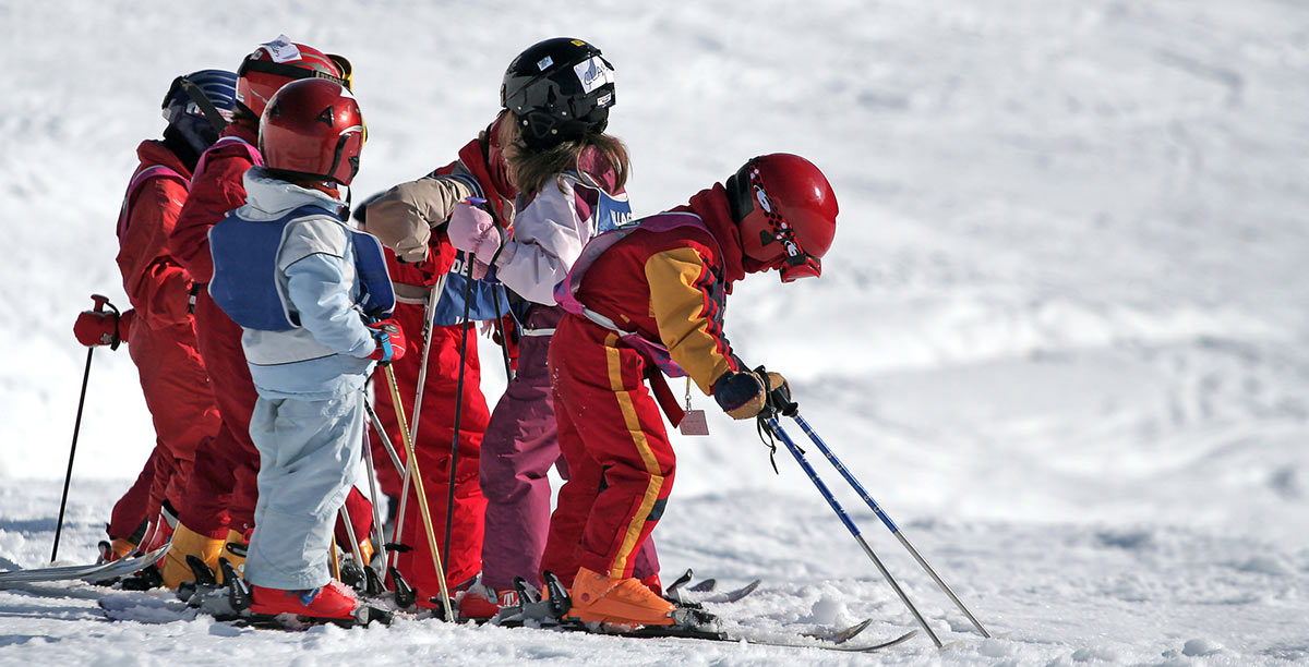 Children with helmet and breastplate try to ski
