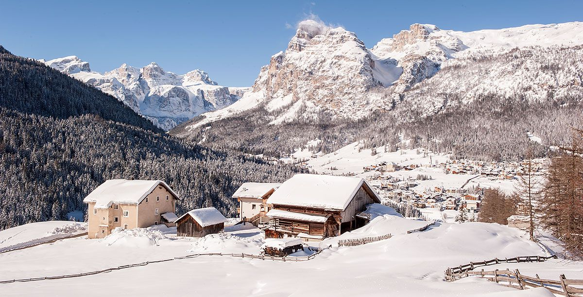 Houses surrounded by snow and high mountains in Alta Badia