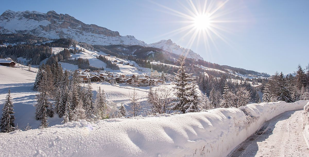 Snow and pine trees and, in the distance, the village of La Villa in Alta Badia
