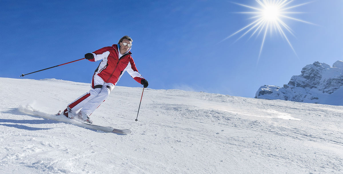 Skier with white suit and red heels on a beautiful sunny day