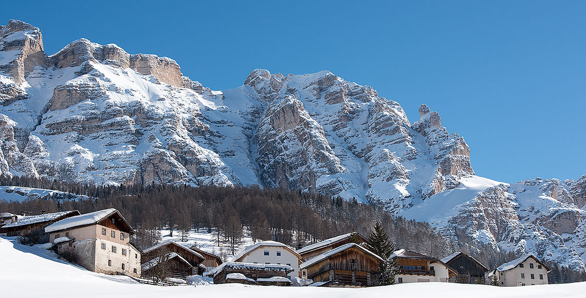Houses in the village of San Cassiano capped at the foot of a high mountain