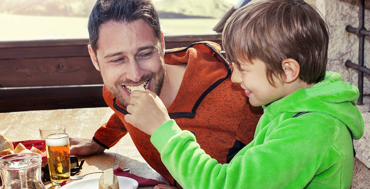 Child let his father taste a piece of his sweet