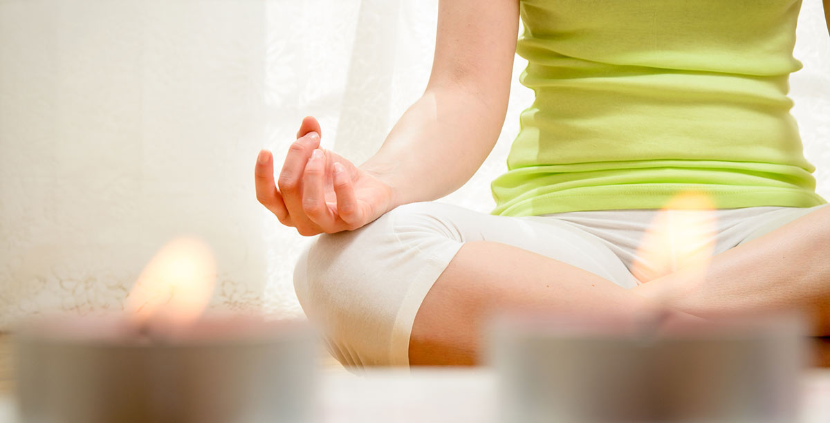 Woman with green shirt and white pants doing meditation